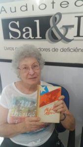 Fotografia de Narhua sorrindo com o livro em mãos