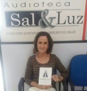 ledora Regina Mello sorrindo com o livro em mãos