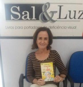Ledora Regina Mello com o livro em mãos sorrindo