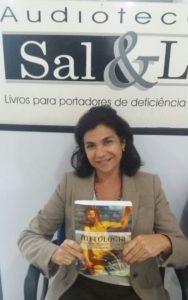 Foto de Valéria Siniscalchi segurando o livro sentada e sorridente